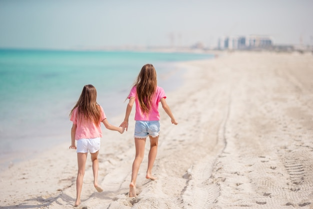 Małe szczęśliwe śmieszne dziewczyny bawią się razem na tropikalnej plaży. słoneczny dzień z deszczem w morzu