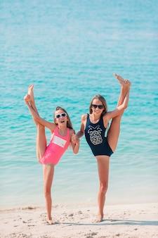 Małe szczęśliwe śmieszne dziewczyny bawią się razem na tropikalnej plaży.