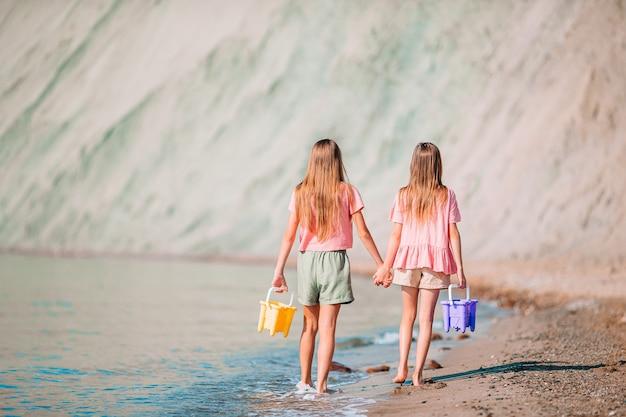 Małe szczęśliwe, zabawne dziewczyny świetnie się bawią na tropikalnej plaży, grając razem. słoneczny dzień z deszczem w morzu
