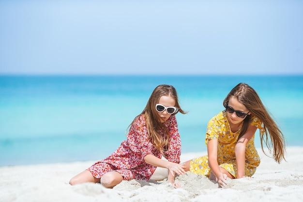Małe szczęśliwe, zabawne dziewczyny świetnie się bawią na tropikalnej plaży, grając razem