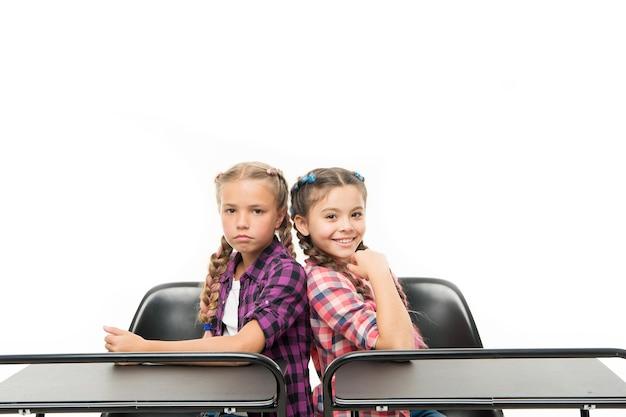 Małe szkolne przyjaciółki uczą się razem. koledzy z klasy siedzą przy biurku. powrót do szkoły. koncepcja szkoły prywatnej. nauczanie indywidualne. edukacja w szkole podstawowej. ciesz się procesem nauki.