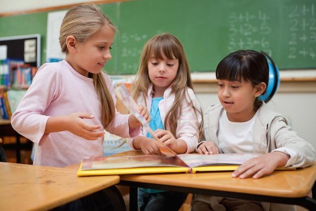 Małe uczennice czytające bajkę swoim kolegom z klasy