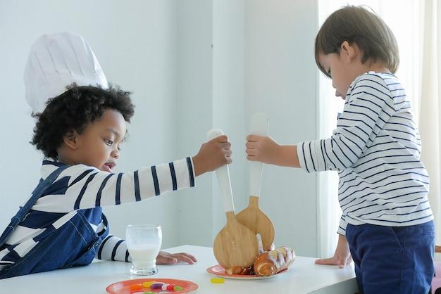Małe urocze dzieci bawiące się zabawkową kuchnią w kapeluszu szefa kuchni. zabawki edukacyjne dla dzieci.