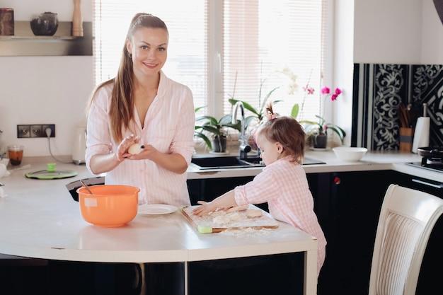 Małe urocze dziecko pomaga rodzicowi z ciastem w kuchni