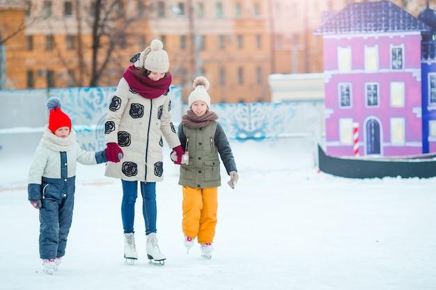 Małe urocze dziewczynki z matką uczące się jazdy na lodowisku