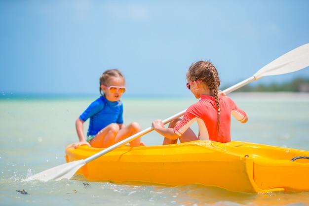 Małe urocze dziewczyny cieszy się kajakarstwo na żółtym kajaku