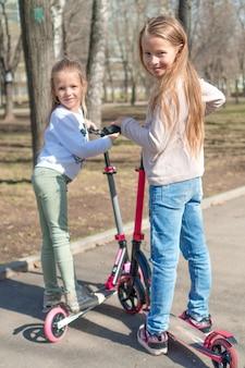 Małe urocze dziewczyny jedzie na hulajnoga w parku outdoors