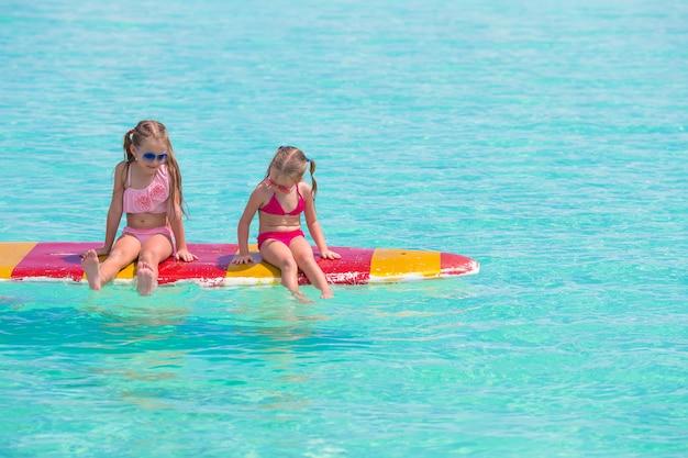 Małe urocze dziewczyny na desce surfingowej w turkusowym morzu