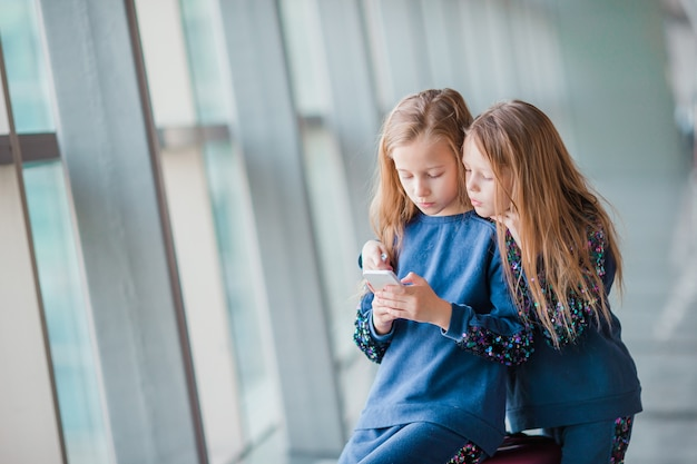 Małe urocze dziewczyny na lotnisku czekają na wejście na pokład i granie z laptopem