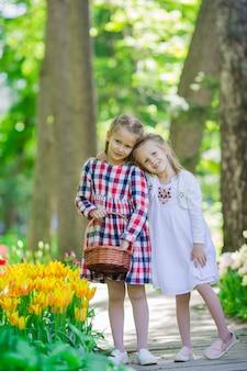 Małe urocze dziewczyny spacerujące w bujnym ogrodzie tulipanów