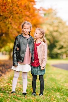 Małe urocze dziewczyny w ciepły słoneczny jesienny dzień na zewnątrz