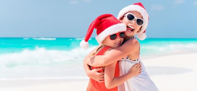 Małe urocze dziewczyny w czapkach świętego mikołaja podczas wakacji na plaży bawią się razem