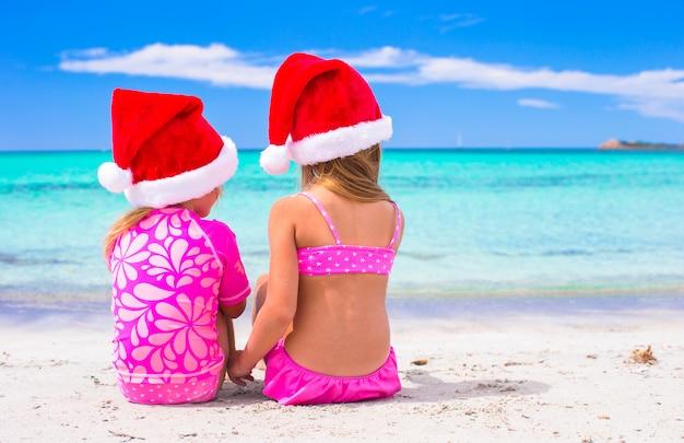 Małe urocze dziewczyny w czapkach świętego mikołaja podczas wakacji na plaży