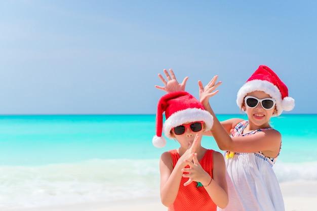 Małe urocze dziewczyny w kapeluszach santa podczas wakacji na plaży dobrze się bawią
