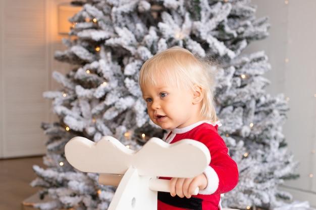Małe uśmiechnięte dziecko siedzi na zabawkowym koniu w pobliżu choinki w świątecznie urządzonym domu