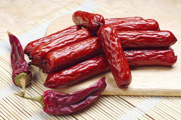 Małe wędzone kiełbaski i suche papryczki chili na desce do krojenia