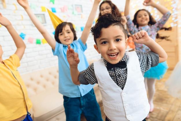 Małe, wesołe dzieci tańczą na przyjęciu urodzinowym.