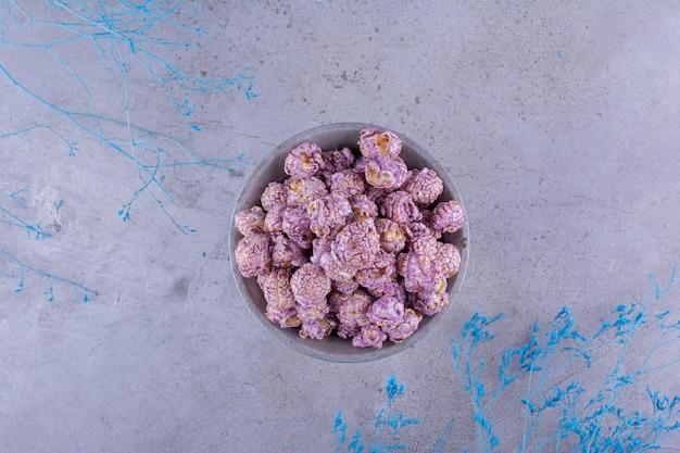 Małe wiaderko wypełnione cukierkami popcorn obok ozdobnych gałązek na marmurowym tle. zdjęcie wysokiej jakości