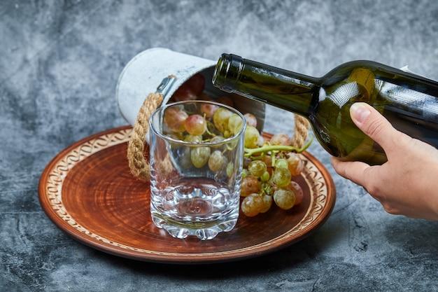 Małe wiaderko z winogronami wewnątrz ceramicznego talerza i ręczne nalewanie wina do kieliszka na marmurze.