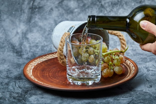 Małe wiaderko z winogronami wewnątrz ceramicznego talerza i ręcznie nalewanie wina do kieliszka na marmurowym tle