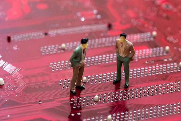 Małe zabawki ludzi są na czerwonej płycie głównej.