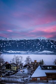 Małe zaśnieżone domy w mieście z niesamowitym niebem i górami