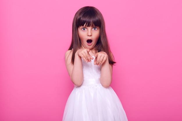 Małe zdumione dziecko płci żeńskiej w białej sukience, patrząc z otwartymi ustami, wskazując na aparat palcami wskazującymi, widzi coś niesamowitego, odizolowane na różowej ścianie