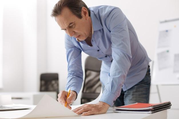 Małe zmiany. skoncentrowany starszy profesjonalny inżynier stojący w pobliżu stołu i rysujący plan podczas pracy w biurze