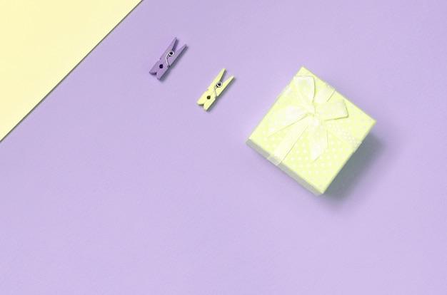 Małe żółte pudełko i dwa kołki leżą na tle tekstury papieru w pastelowych kolorach żółtym i fioletowym