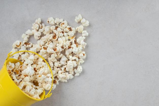 Małe żółte wiaderko wylewa świeży popcorn na marmurowy stół.