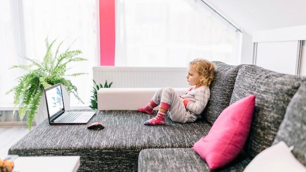 Małej dziewczynki dopatrywania film na kanapie
