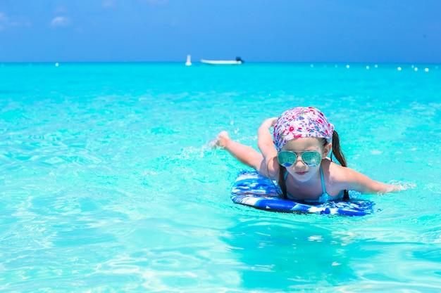 Małej dziewczynki dopłynięcie na surfboard w turkusowym morzu