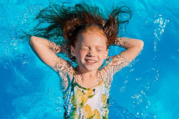 Małej dziewczynki dopłynięcie w basenie w lecie