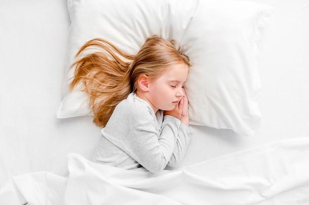 Małej dziewczynki dosypianie w białym łóżku