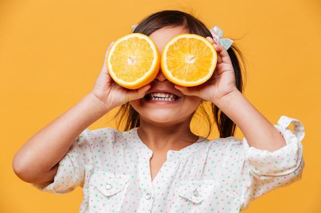 Małej dziewczynki dziecko zakrywa oczy z pomarańcze.