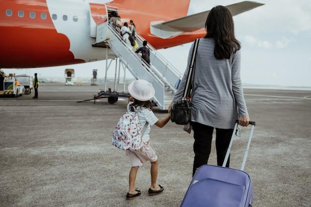 Małej dziewczynki i matki mienia ręki chodzą w kierunku samolotu