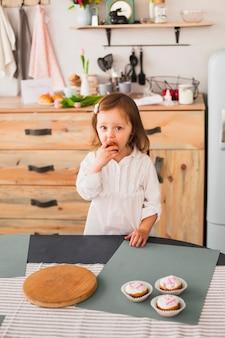 Małej dziewczynki łasowania babeczka