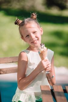 Małej dziewczynki łasowania lody outdoors przy latem w plenerowej kawiarni