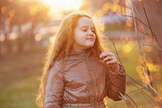 Małej dziewczynki mienia potomstw zielona gałąź w świetle słonecznym.