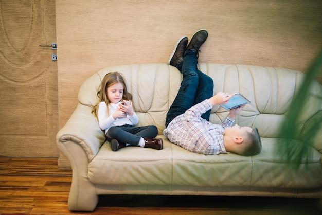 Małej dziewczynki obsiadanie blisko jego brata patrzeje cyfrową pastylkę na kanapie w domu