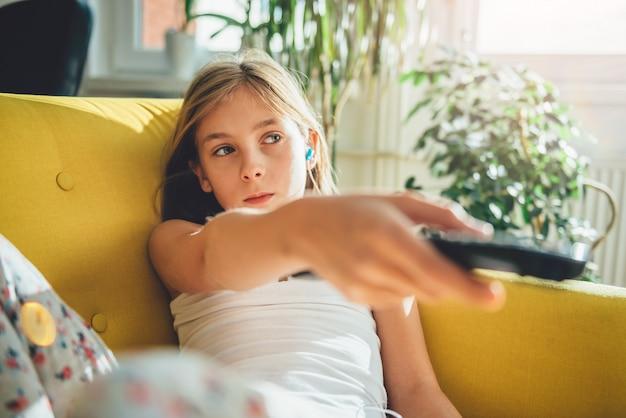 Małej dziewczynki obsiadanie na kanapie i oglądać tv
