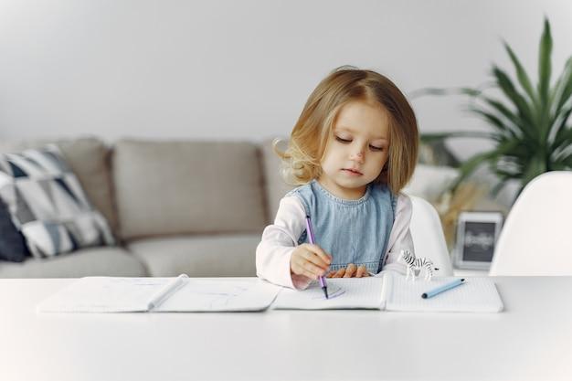 Małej dziewczynki obsiadanie na stole z książkami