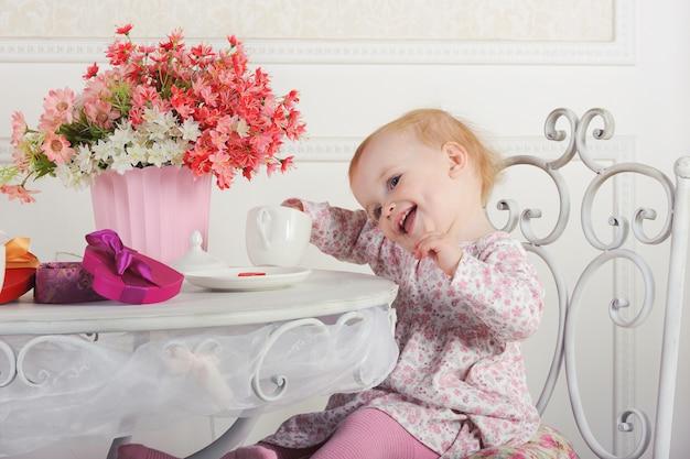 Małej dziewczynki obsiadanie przy stołem z herbatą i dekoracjami, portret, zakończenie