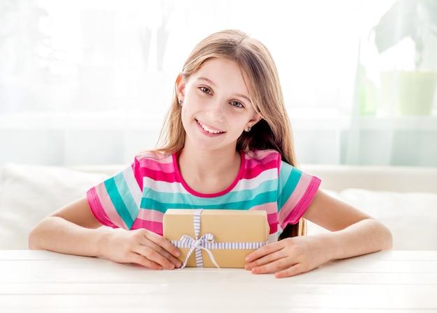Małej dziewczynki obsiadanie przy stołu i mienia prezenta pudełkiem