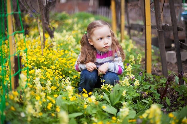 Małej dziewczynki obsiadanie w żółtych kwiatach w wiosna ogródzie