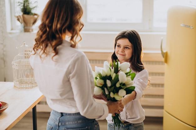 Małej dziewczynki powitania matka z kwiatami na matka dniu