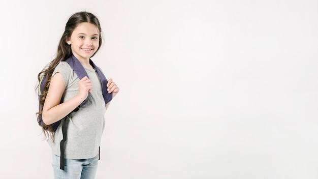Małej Dziewczynki Pozycja Z Schoolbag W Studiu Premium Zdjęcia
