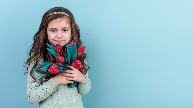 Małej dziewczynki pozycja z zabawkarskimi kwiatami
