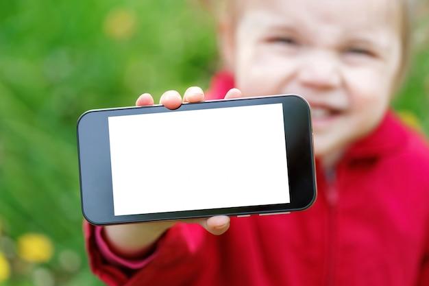 Małej dziewczynki przedstawienie komórki inteligentny ekran telefonu z pustą białą kopię miejsca.