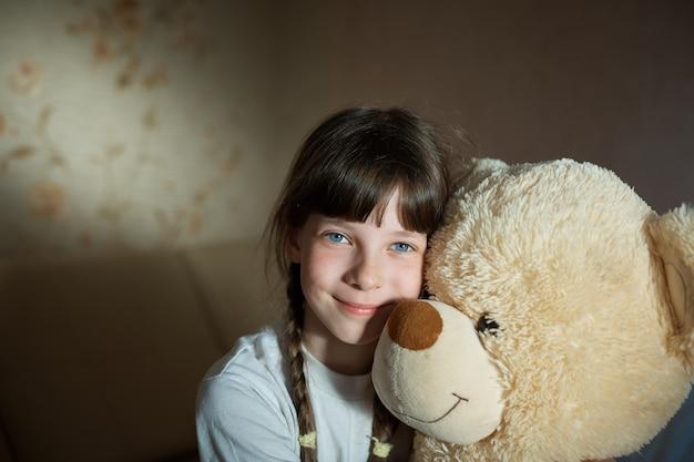 Małej dziewczynki przytulenia miś salowy w jej pokoju, oddania pojęcie, duża niedźwiedź zabawka